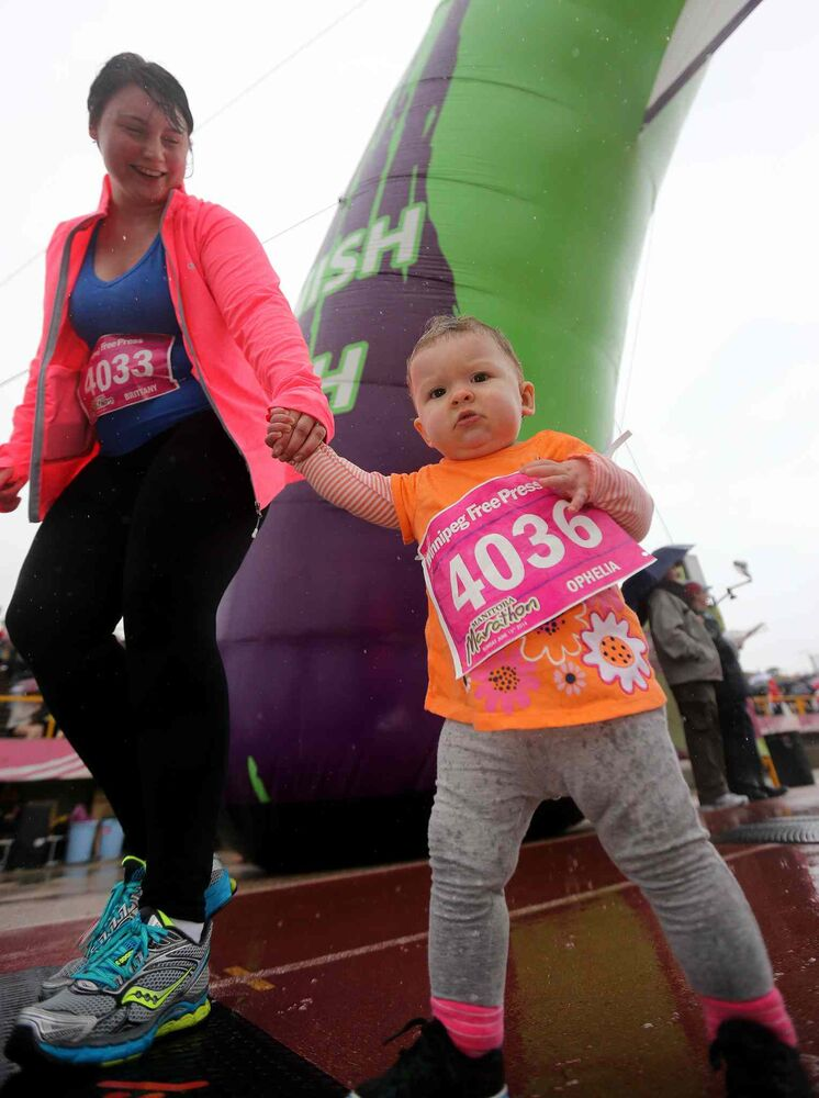 Brittany Savoie and her daughter, Ophelia Savoie, 1, near the finish line of the Winnipeg Free Press 10-kilomtre run. (Trevor Hagan / Winnipeg Free Press)