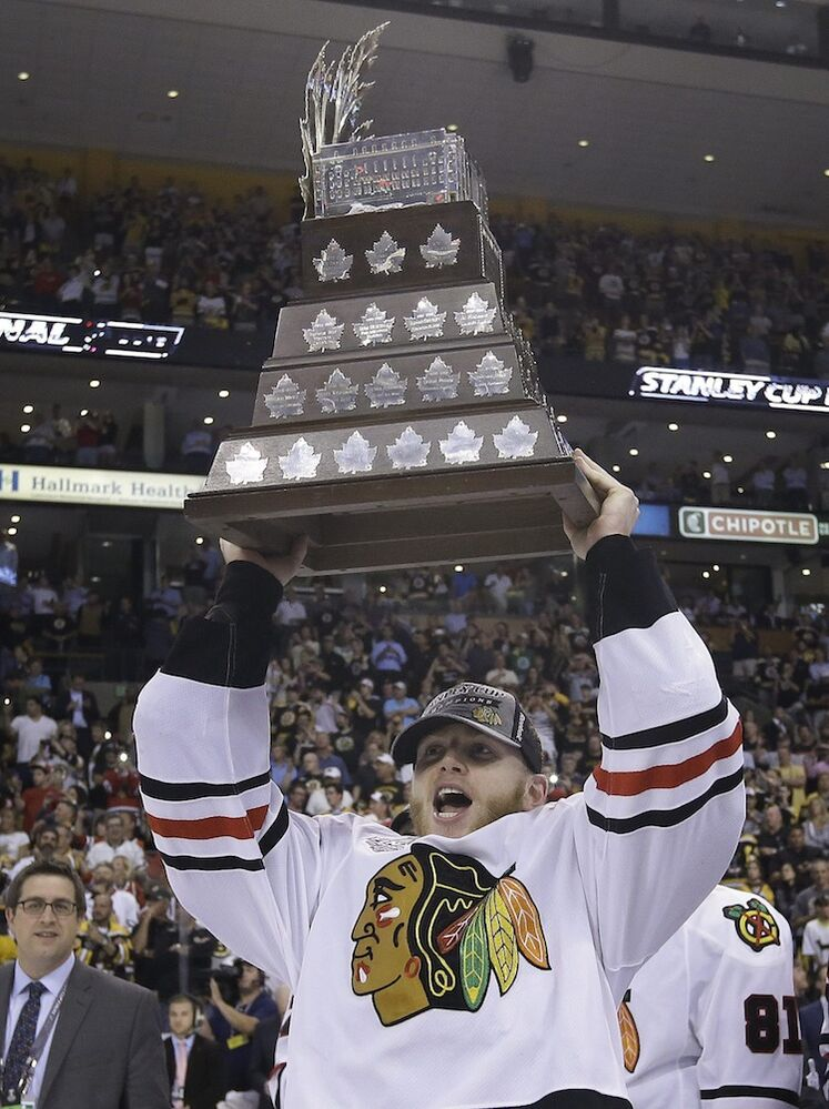 Chicago Blackhawks winger Patrick Kane hoists the Conn Smythe trophy, awarded to the most valuable player in the playoffs. (Elise Amendola / The Associated Press)