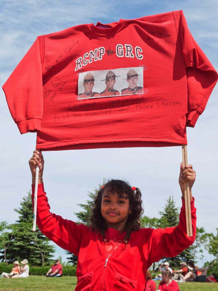A young girl holds up and RCMP sweatshirt with words of encouragement and photos of slain officers attached during the funeral procession in Moncton. (Marc Grandmaison / The Canadian Press)