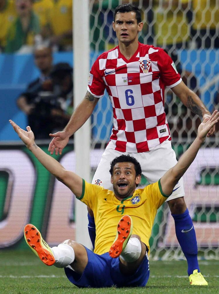Brazil's Frederico Chaves Guedes, bottom, raises his arms after a penalty was called against Croatia's Dejan Lovren, top, by referee Yuichi Nishimura, from Japan, during the group A World Cup soccer match between Brazil and Croatia in the opening game of the tournament at the Itaquerao Stadium in Sao Paulo, Brazil on Thursday. Brazil was issued a penalty kick following the play leading to a goal by Neymar da Silva Santos Júnior helping Brazil to a 3-1 victory.  (Frank Augstein / The Associated Press)