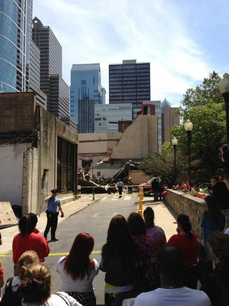 Police keep onlookers behind yellow tape near the collapsed building. Witnesses said they heard a loud rumbling sound immediately before the collapse. (Jonathan Hudson / The Associated Press)