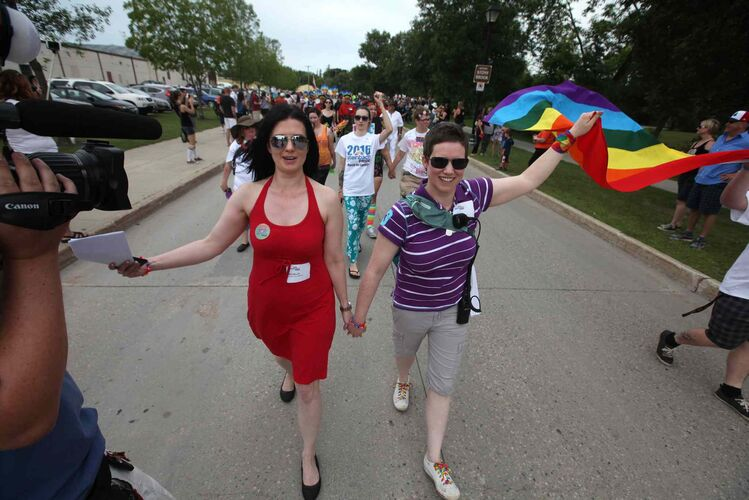 Michelle McHale and her partner Karen Phillips hold hands as they lead thousands of supporters down the streets of Steinbach. - RUTH BONNEVILLE / WINNIPEG FREE PRESS