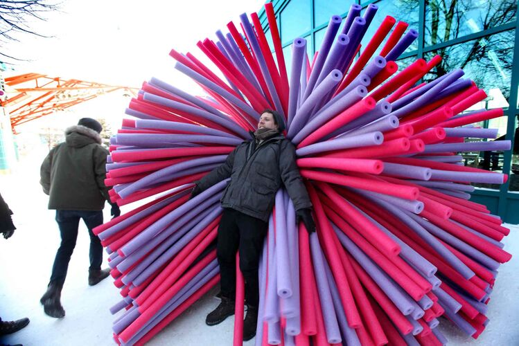 Asron Hendershott of Raw Design Inc. designers cozies up in one of their three unique and colourful warming huts that will be available for the public to try out along the River Trail soon during the annual Warming Huts: An Art and Architecture Competition on Ice at the Forks.  - Ruth Bonneville / Winnipeg Free Press