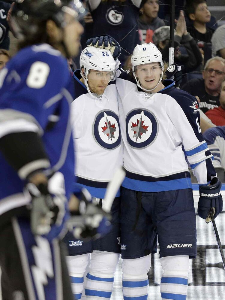 Winnipeg Jets winger Blake Wheeler (centre) celebrates his first-period goal against the Tampa Bay Lightning with teammate Jacob Trouba (right) during the first period. (Chris O'Meara / The Associated Press)