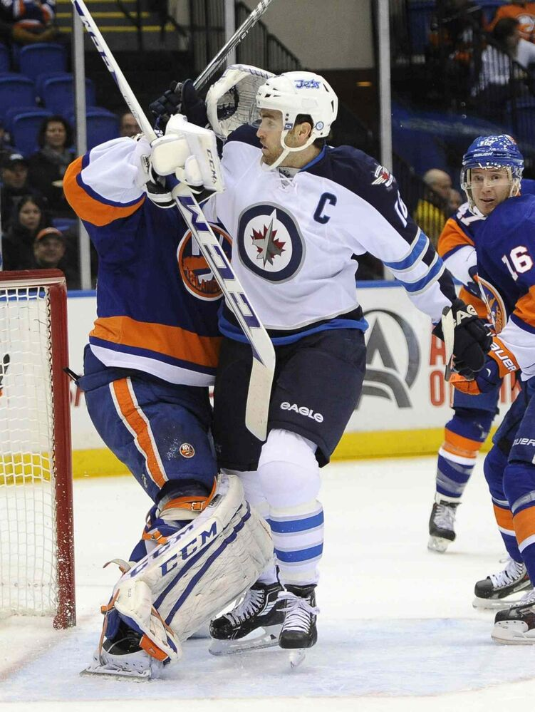 New York Islanders goalie Kevin Poulin (left) battles with Winnipeg Jets forward Andrew Ladd in front of the net in the first period.