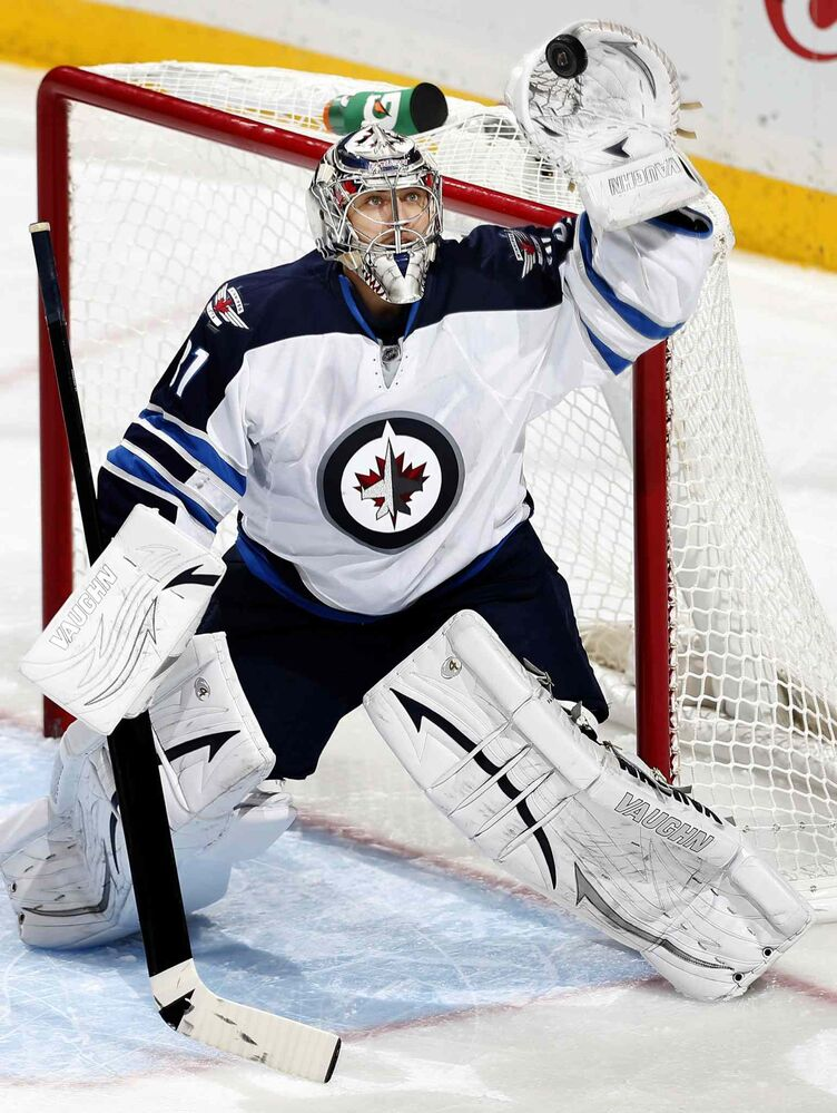 Winnipeg Jets goalie Ondrej Pavelec gloves a flying puck during the second period. (Carlos Gonzalez / Minneapolis Star Tribune / MCT)