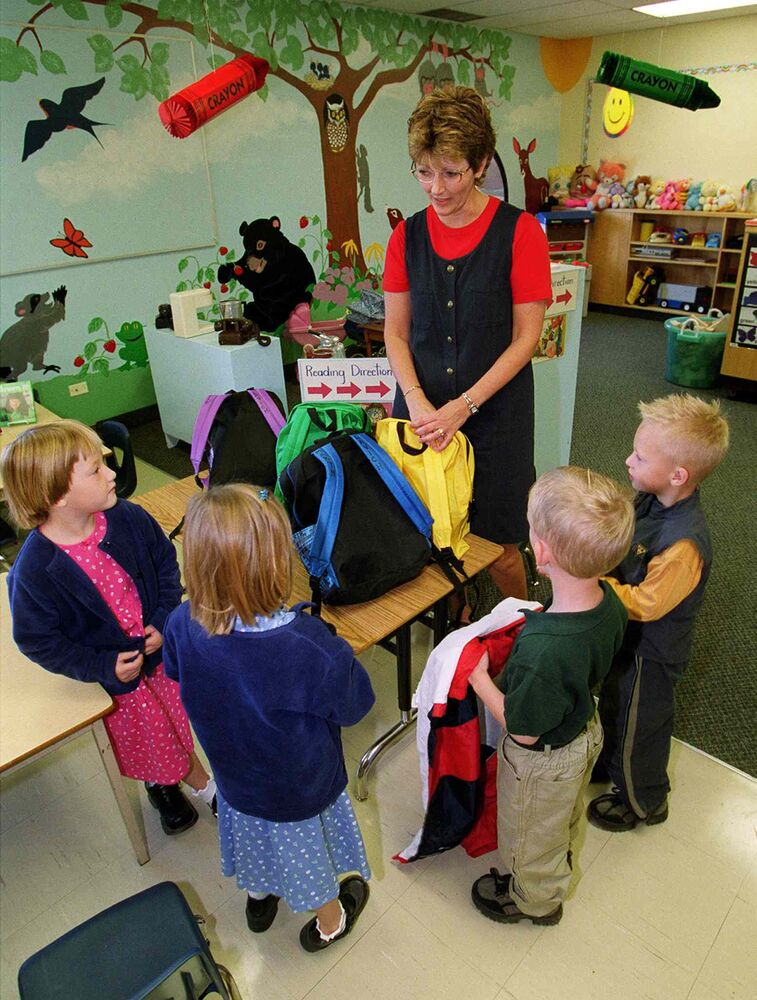 On their first day of school, the Lavich quadruplets meet kindergarten teacher Sandra Grobb at R.J. Waugh Elementary School on Aug. 31, 2001. (JEFF DE BOOY / WINNIPEG FREE PRESS FILES)