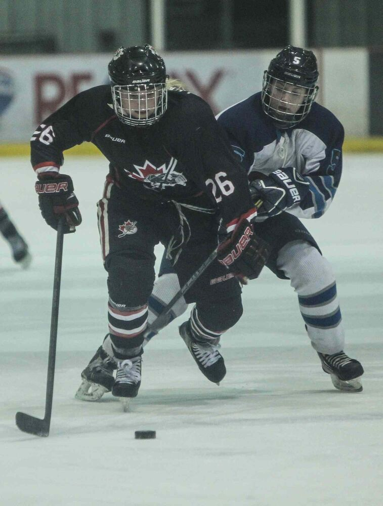 The Shaftesbury Titans' Sydney Mullin (right) tries to slow down the POEs' Tirra Lemoine during the second period. (MIKE DEAL / WINNIPEG FREE PRESS)