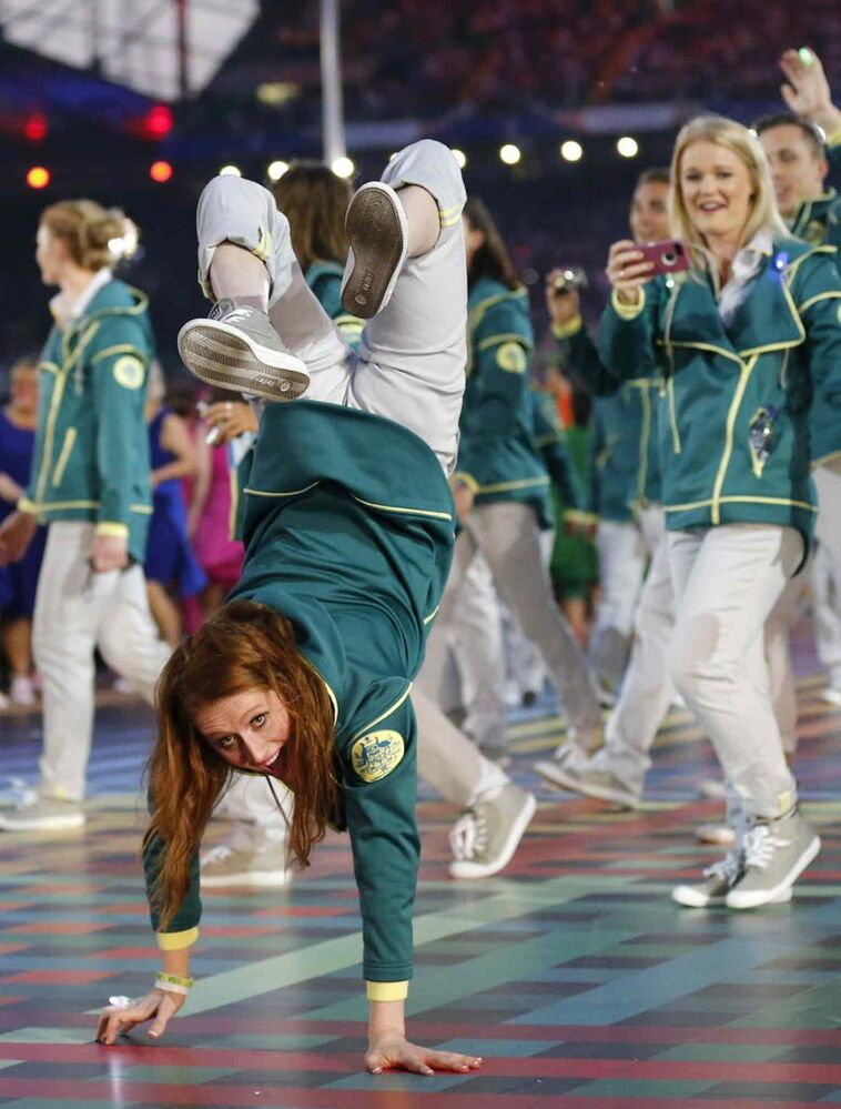 An Australian athlete does a handstand as she arrives with her teammates during the opening ceremony for the Commonwealth Games 2014 in Glasgow, Scotland on Wednesday. (Frank Augstein / The Associated Press)