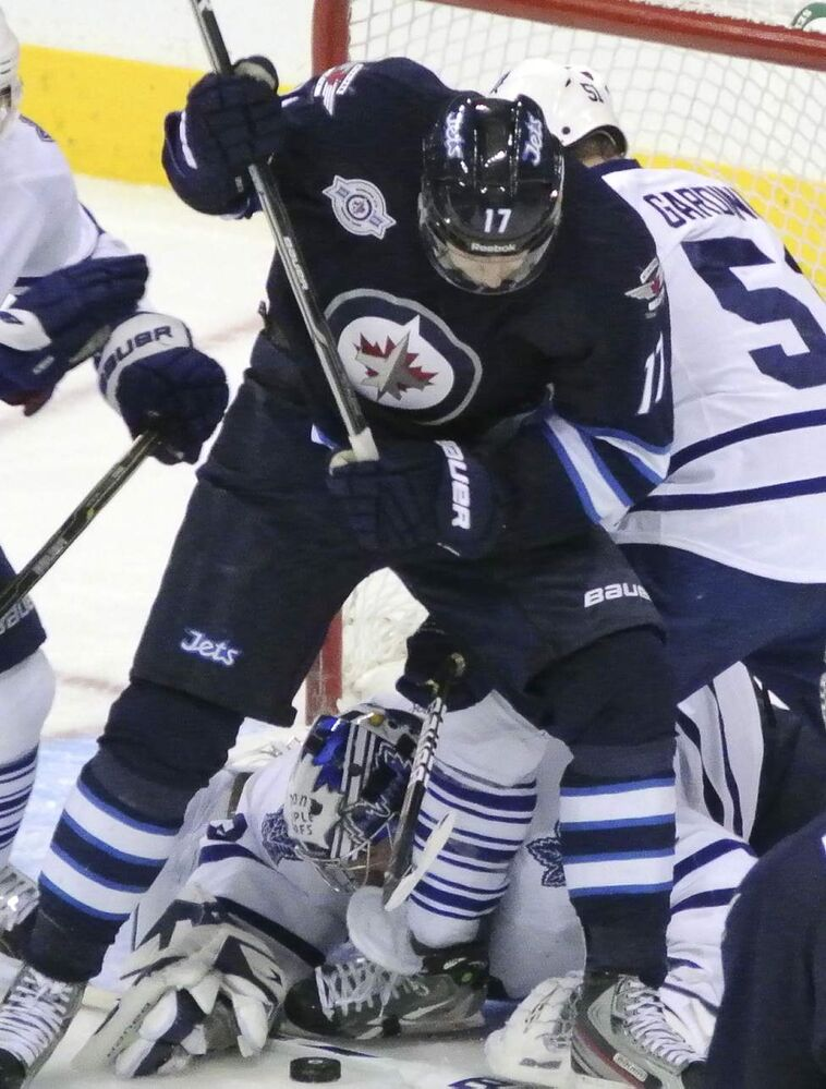 Toronto Maple Leafs' goaltender James Reimer tries to get his glove on the puck while Winnipeg Jets' Eric Fehr (17) tries to keep his position in front of the net in the third period.  December 31, 2011 -  (MIKE DEAL / WINNIPEG FREE PRESS)