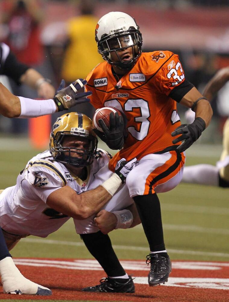 Winnipeg Blue Bombers wide receiver Kito Poblah hangs onto B.C. Lions running back Andrew Harris during second quarter.