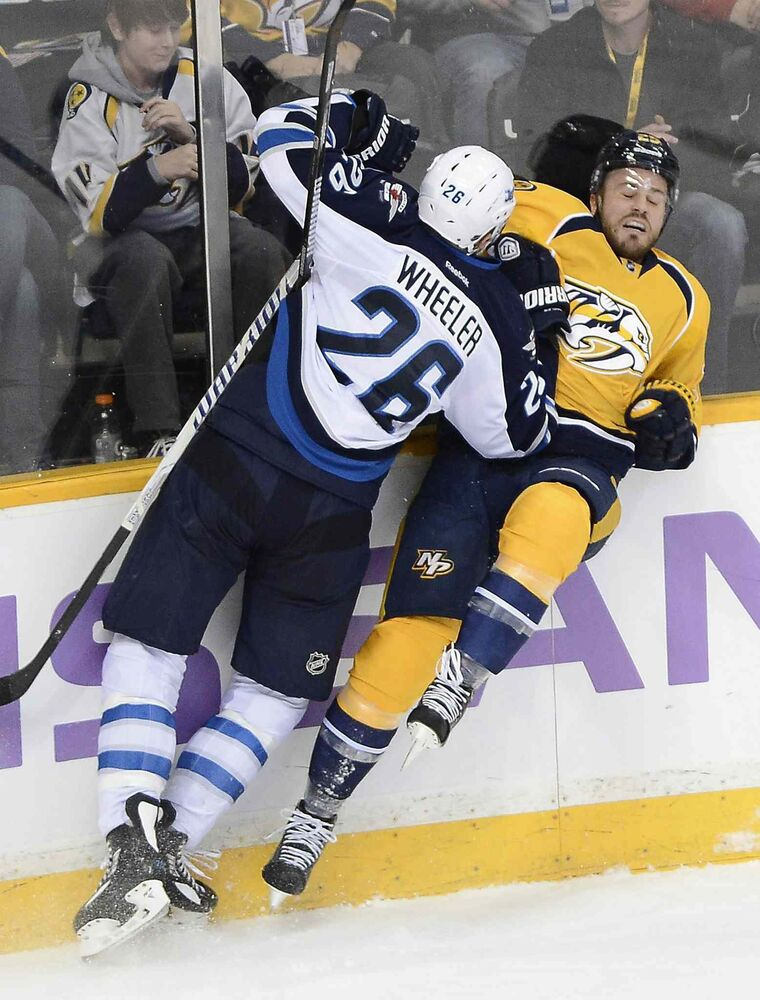 Winnipeg Jets' right wing Blake Wheeler (26) checks Nashville Predators' forward Viktor Stalberg (25) into the boards during the second period of Saturday's game.