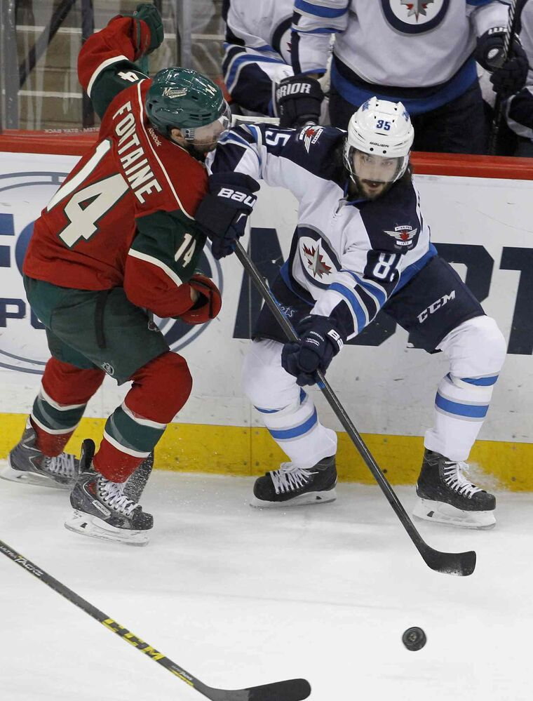 Winnipeg Jets centre Mathieu Perreault (85) passes the puck and holds off Minnesota Wild right wing Justin Fontaine (14) during the first period. (Ann Heisenfelt / The Associated Press)