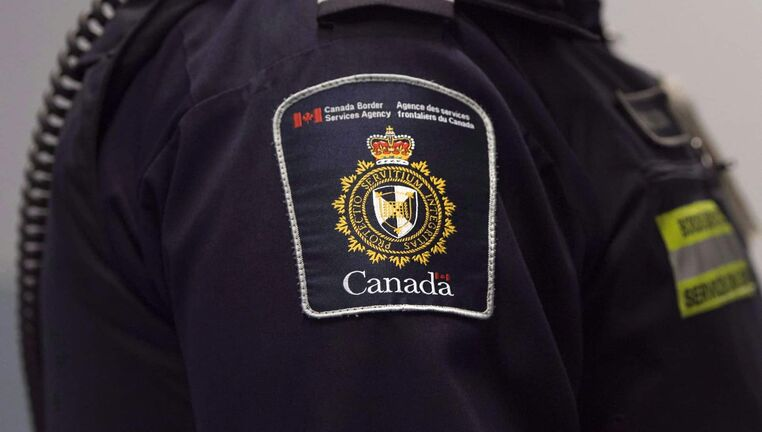 A Canadian Border Services agent stands watch at Pearson International Airport in Toronto on Tuesday, December 8, 2015. A group of doctors, lawyers, legal scholars and human rights organizations is calling on the federal government to halt the rollout of a new policy that will see border officers outfitted in defensive gear when dealing with refugees in detention. THE CANADIAN PRESS/Darren Calabrese