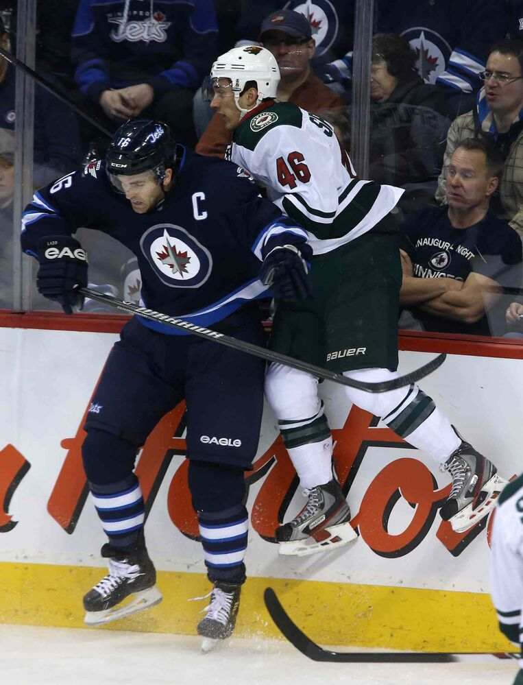 Winnipeg Jets forward Andrew Ladd hits Minnesota Wild's Jared Spurgeon during the first period. (TREVOR HAGAN / WINNIPEG FREE PRESS)