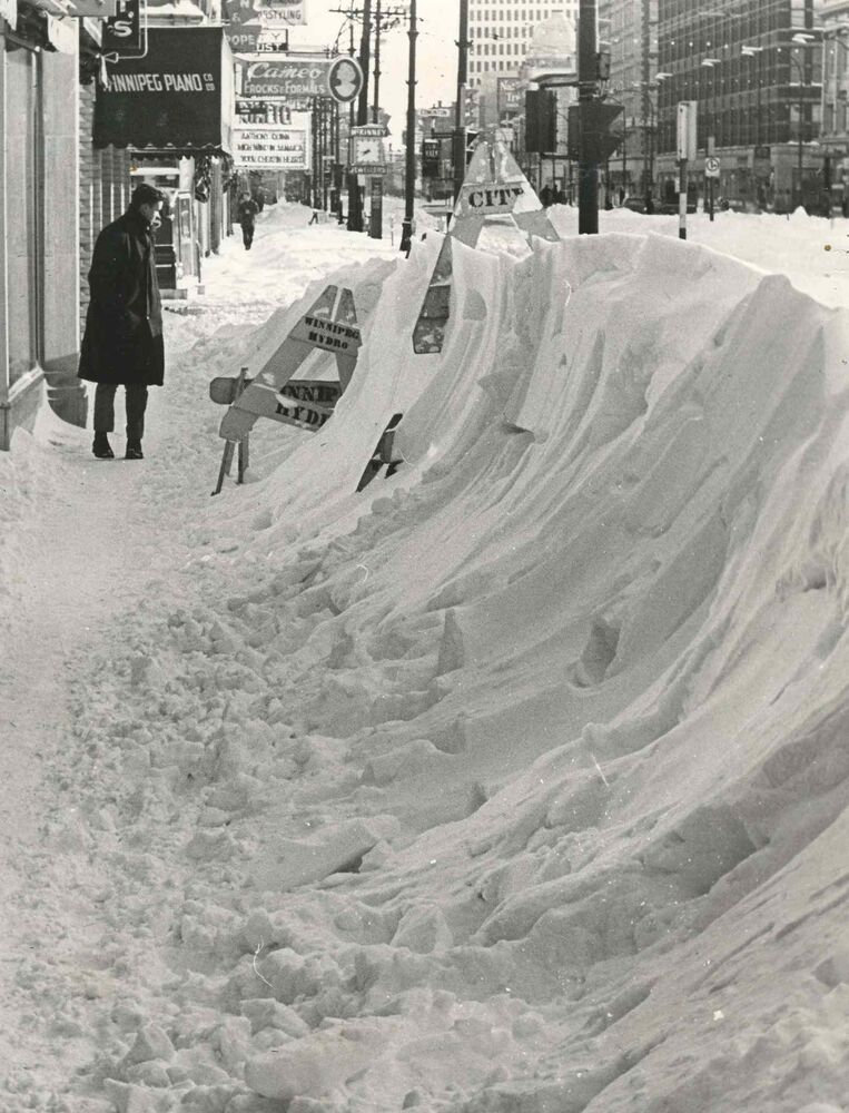 Surveying the results of the blizzard was part of the game for pedestrians along Portage Avenue who gaped in wonderment at snow hurled high along the sidewalks.