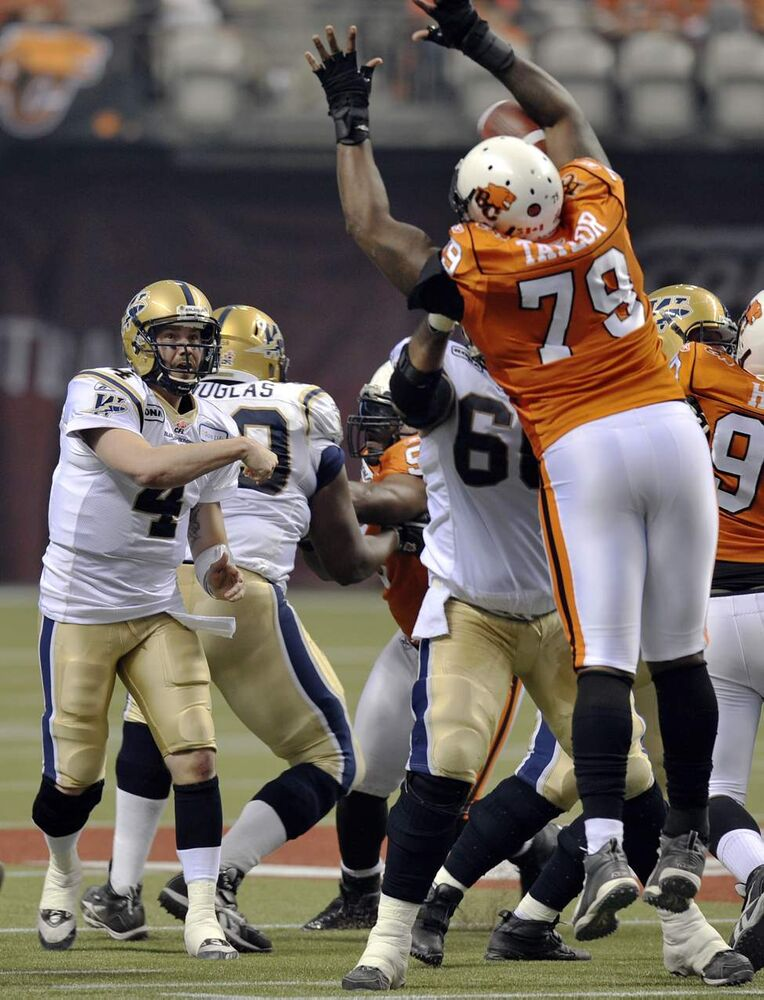 B.C. Lions Eric Taylor blocks a pass by Winnipeg Blue Bombers quarterback Buck Pierce during first-half action of the 2011 Grey Cup final.   (Jason Payne / Postmedia News)