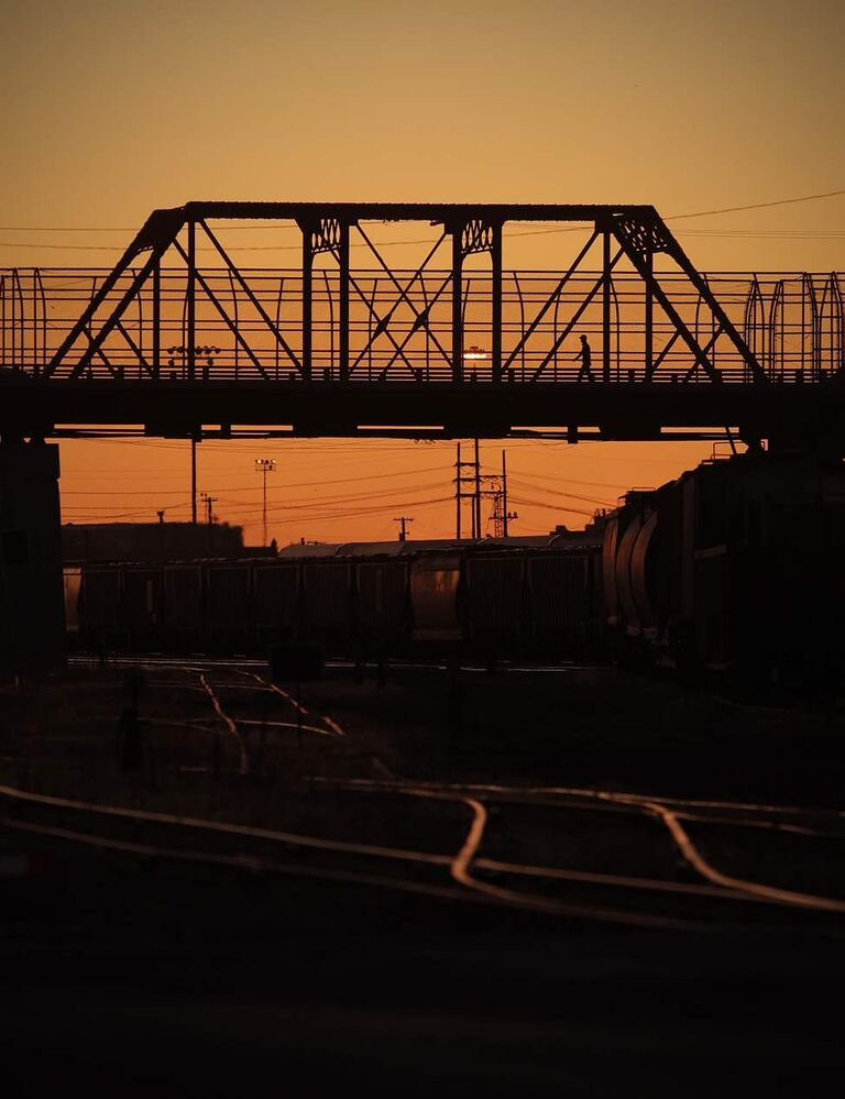 A pedestrian crosses the Arlington bridge during a sunset. July 30, 2011 (John Woods/Winnipeg Free Press)