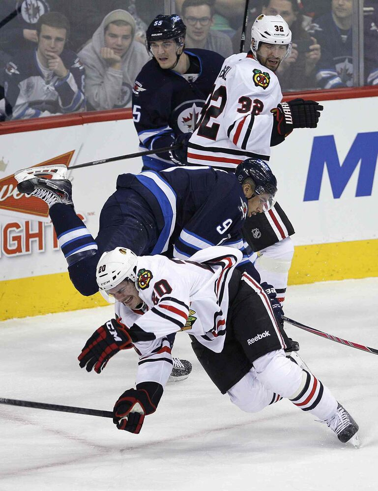Winnipeg Jets forward Evander Kane (9) and Brandon Saad (20) of the Chicago Blackhawks collide as Mark Scheifele (55) and the Blackhawks' Michal Rozsival (32) look on during the first period.