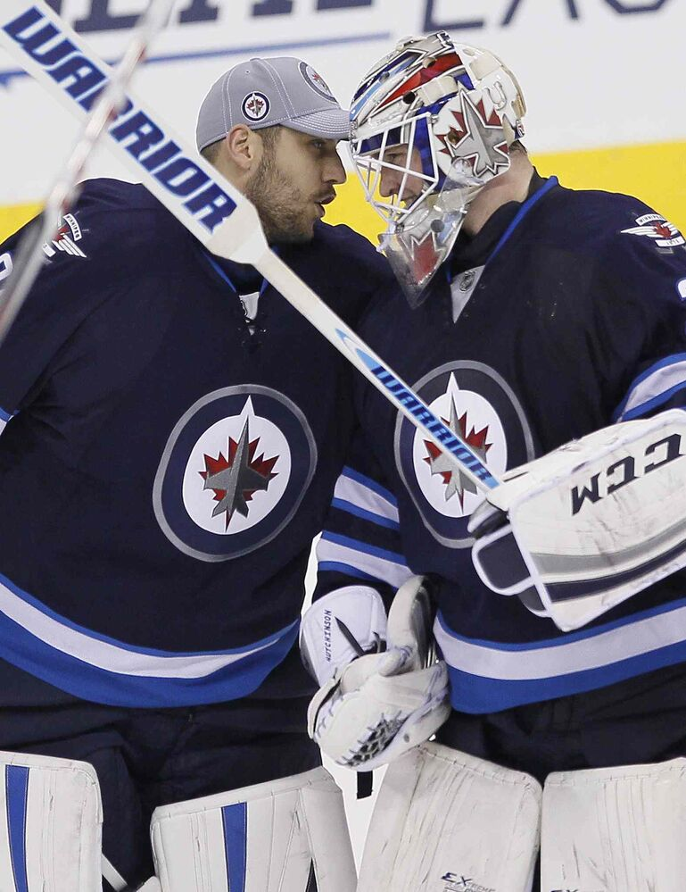 Winnipeg Jets goaltender Michael Hutchinson (34) celebrates his first win in NHL win with Ondrej Pavelec (31) after making the big save on Boston Bruins' Brad Marchand (63) during the shoot out in Winnipeg on Thursday. (John Woods / The Canadian Press)
