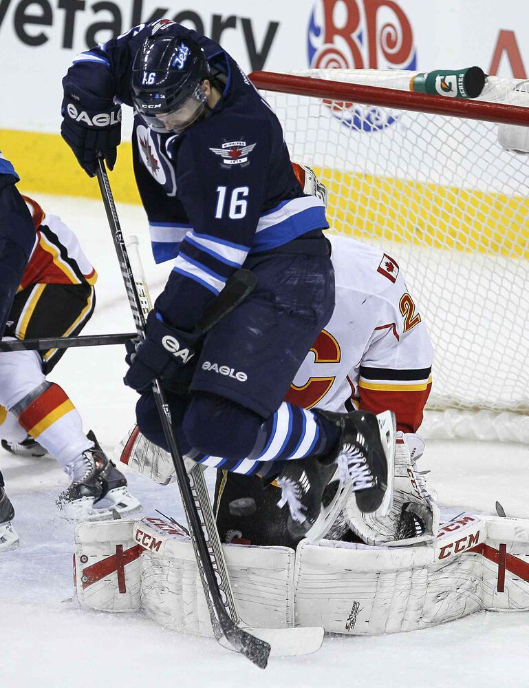 Winnipeg Jets' Andrew Ladd (16) attempts to deflect the shot from the point as Calgary Flames' goaltender Reto Berra (29) tries to save it through Ladd's screen during first period NHL action in Winnipeg on Monday, Nov. 18, 2013.  (John Woods / Winnipeg Free Presss)