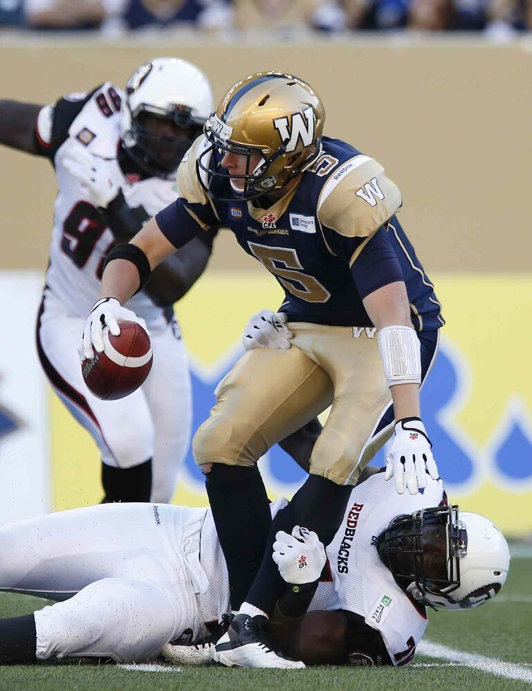 Winnipeg Blue Bombers' quarterback Drew Willy (5) gets sacked by Ottawa Redblacks' Jonathan Williams (75) during the first half Thursday's game.