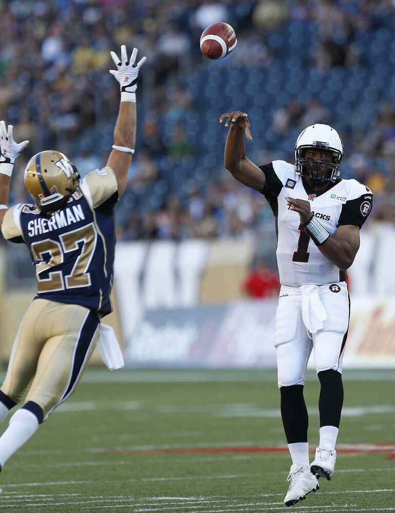Ottawa Redblacks quarterback Henry Burris (1) throws a touchdown pass to Chevon Walker (29) as Winnipeg Blue Bombers' Teague Sherman (27) attempts to knock it down during the first half of Thursday's game.