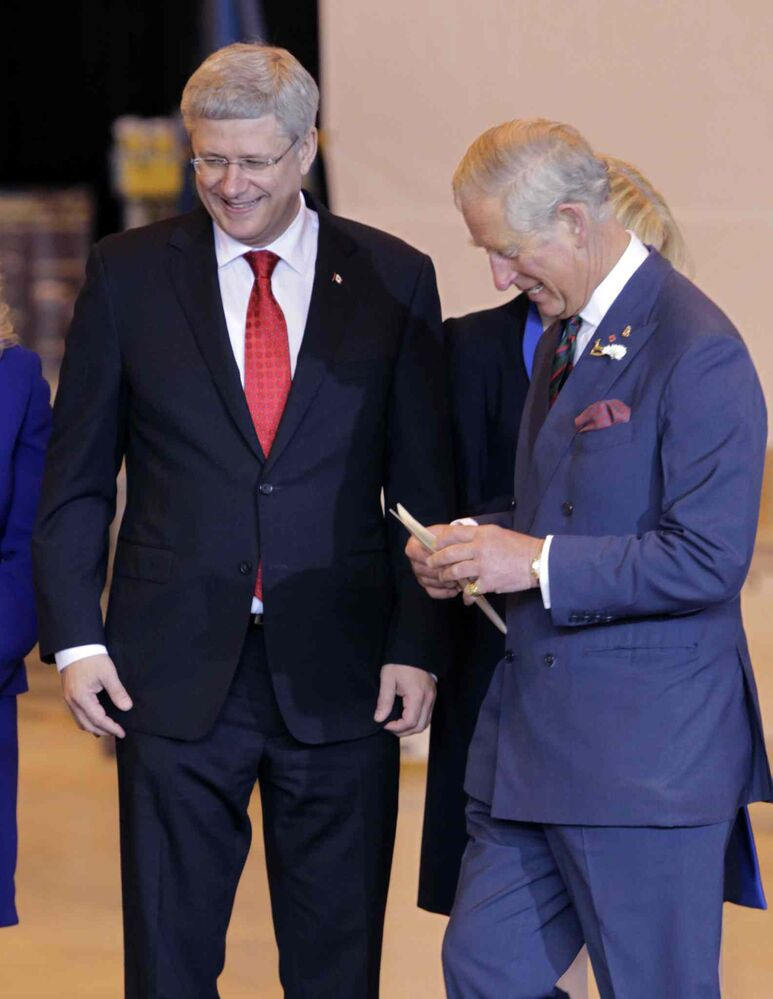 At left, Prime Minister Stephen Harper invites Prince Charles to the podium at the ceremony in the Stevenson Hangar Wednesday morning.  (Wayne Glowacki / Winnipeg Free Press)