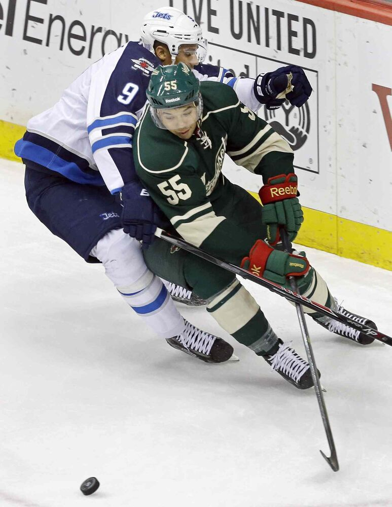 Evander Kane (9) attempts to slow down Mathew Dumba of the Minnesota Wild's as he races around the net for the puck in the first period.