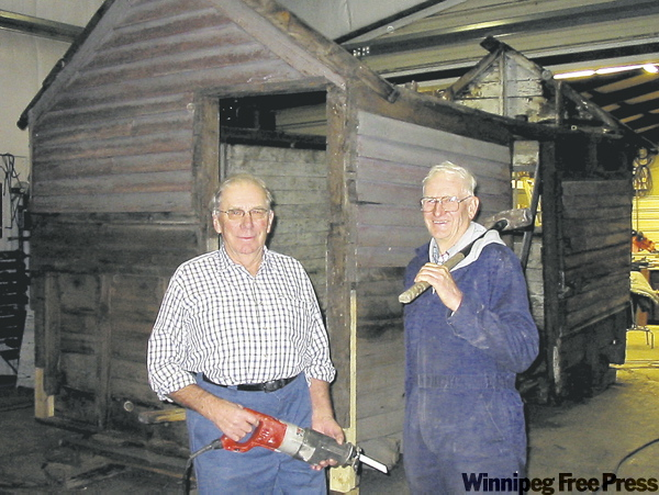 Leonard Pappel (left) and Dick Remus work on restoring original latrine used by North West Mounted Police.