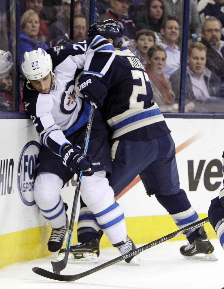 Blue Jackets' Ryan Murray checks Jets grinder Chris Thorburn during the first period Monday night. (Jay LaPrete / The Associated Press)