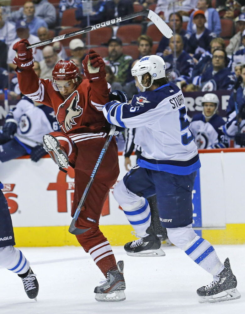 Phoenix Coyotes center Antoine Vermette (50) collides with Winnipeg Jets defenseman Mark Stuart (5). (David Kadlubowski / The Associated Press / The Arizona Republic)