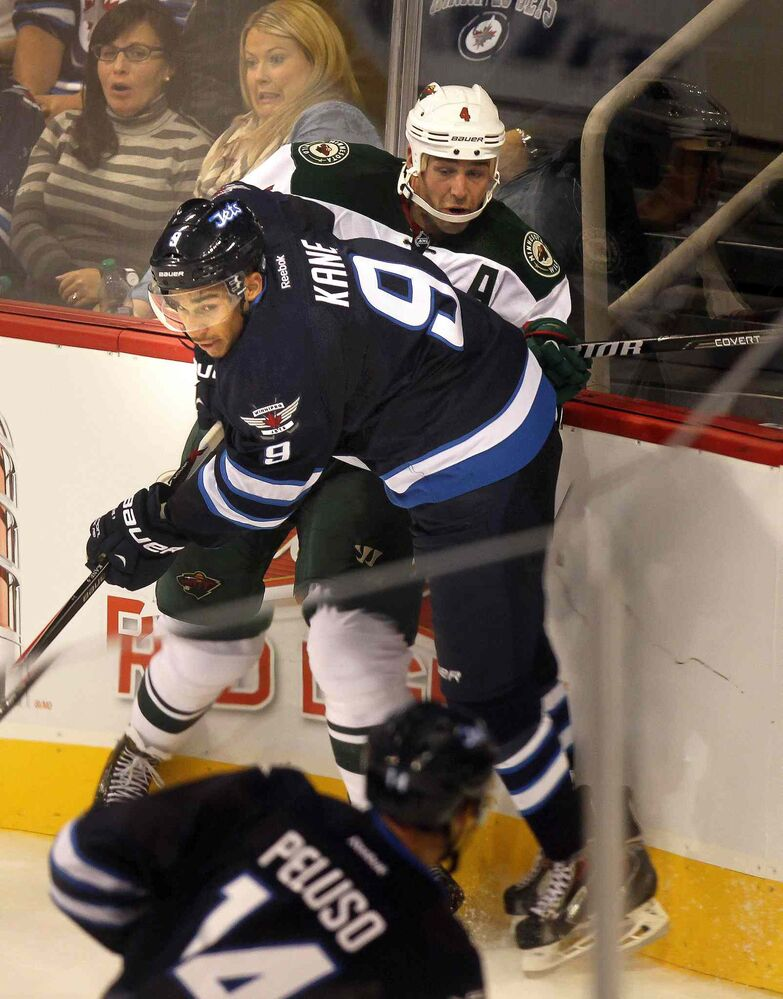 Evander Kane takes out Clayton Stoner of the Minnesota Wild in the third period. (Phil Hossack / Winnipeg Free Press)