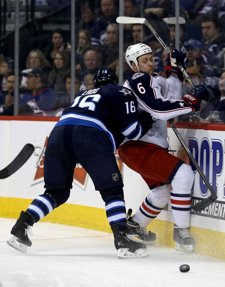 Winnipeg Jets' Andrew Ladd (16) hits Columbus Blue Jackets' Nikita Nikitin (6) into the boards during second period NHL hockey action in Winnipeg Saturday. (Trevor Hagan / Winnipeg Free Press)