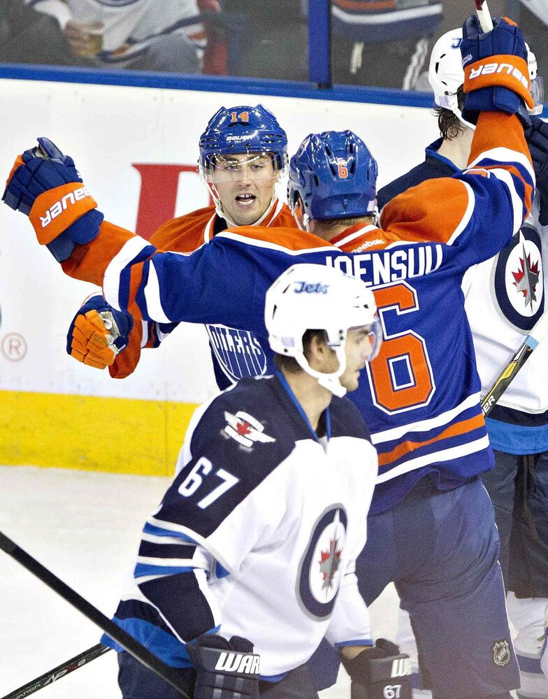 Winnipeg Jets' Michael Frolik (67) skates past as Edmonton Oilers' Jordan Eberle (14) and teammate Jesse Joensuu (6) celebrate a goal during second period NHL hockey action in Edmonton Tuesday. (Jason Franson / The Canadian Press)