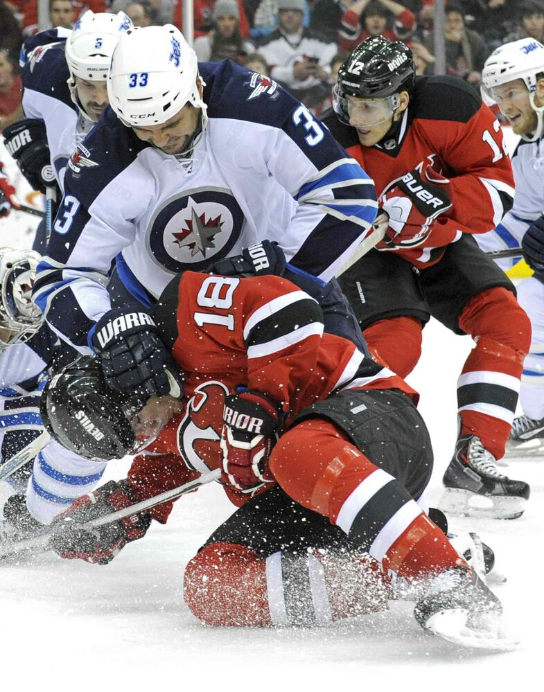 Winnipeg Jets defenceman Dustin Byfuglien checks New Jersey Devils forward Steve Bernier during the second period. (BILL KOSTROUN / THE ASSOCIATED PRESS)