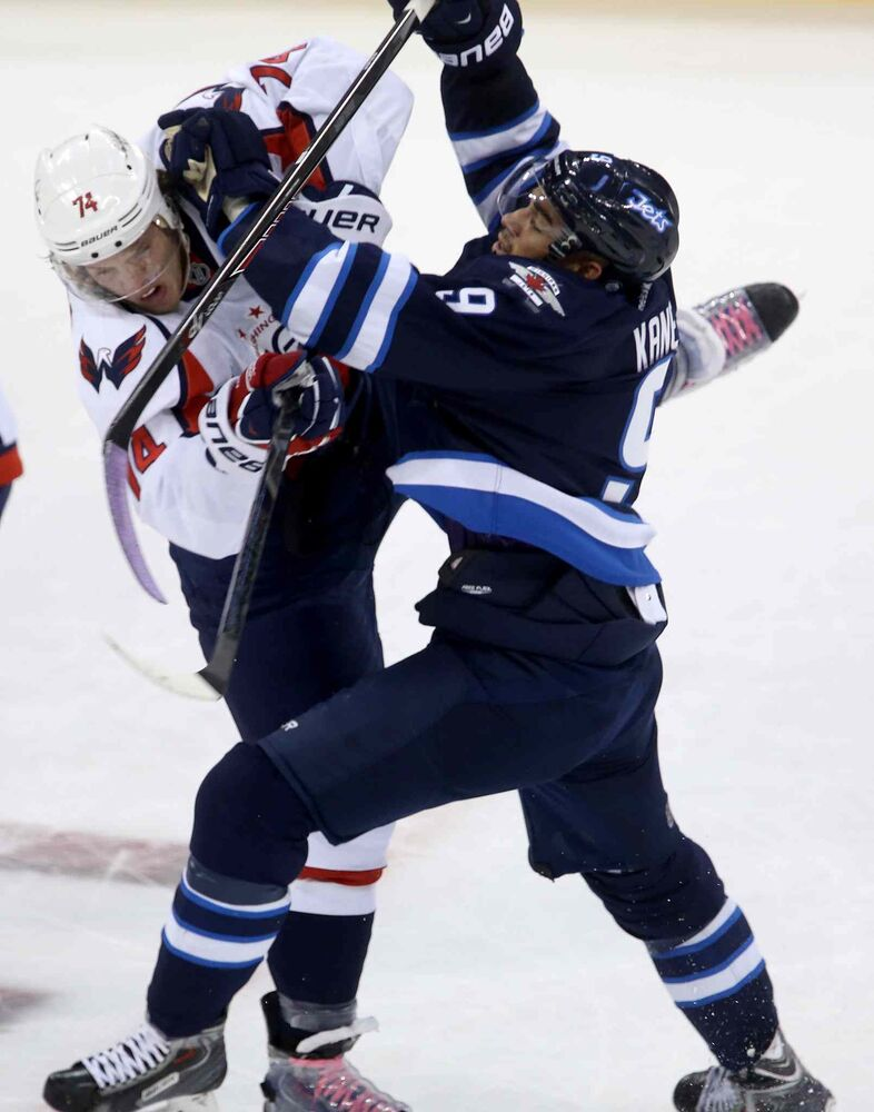 Winnipeg Jets forward Evander Kane collides with Washington Capitals' John Carlson during the first period. (TREVOR HAGAN / THE CANADIAN PRESS)
