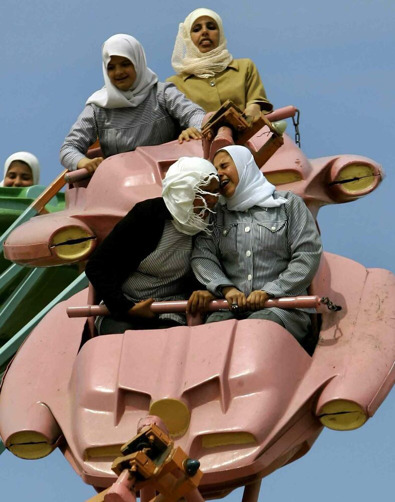 March 26, 2006:  Palestinians enjoy a ride at an amusement park outside Gaza City.  (Anja Niedringhaus / The Associated Press)