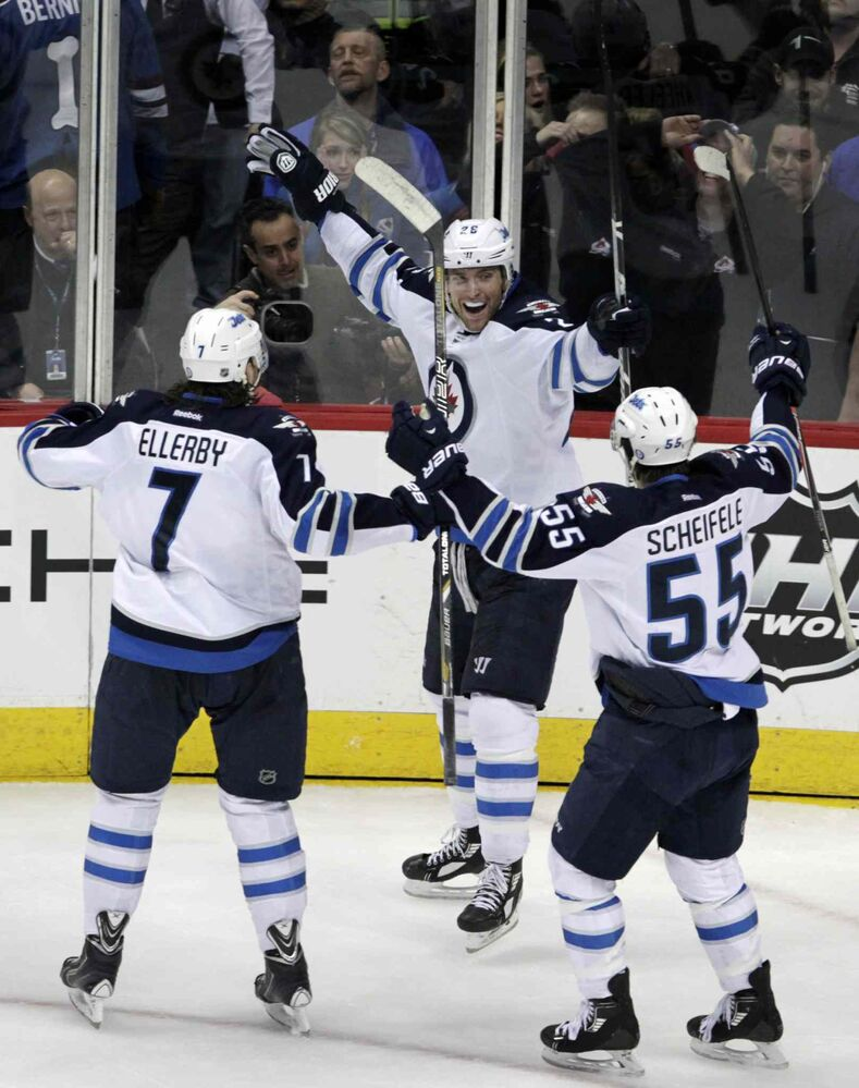 Winnipeg Jets winger Blake Wheeler (centre) celebrates scoring the game-winning goal with Jets defenceman Keaton Ellerby (left) and centre Mark Scheifele during the final seconds of overtime. (Joe Mahoney / The Associated Press)