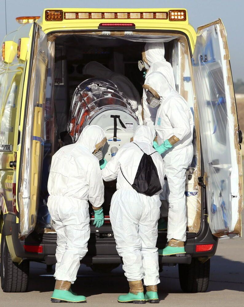 Aid workers and doctors transfer Miguel Pajares, a Spanish priest who was infected with the Ebola virus while working in Liberia. (Spanish Defense Ministry / The Associated Press )