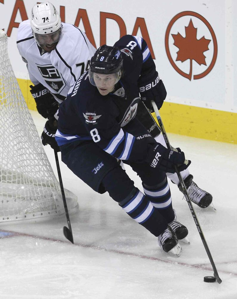 Jacob Trouba (8) takes control of the puck from behind the Jets' net while Los Angeles Kings' Dwight King (74) is hot on his heels in the second period.