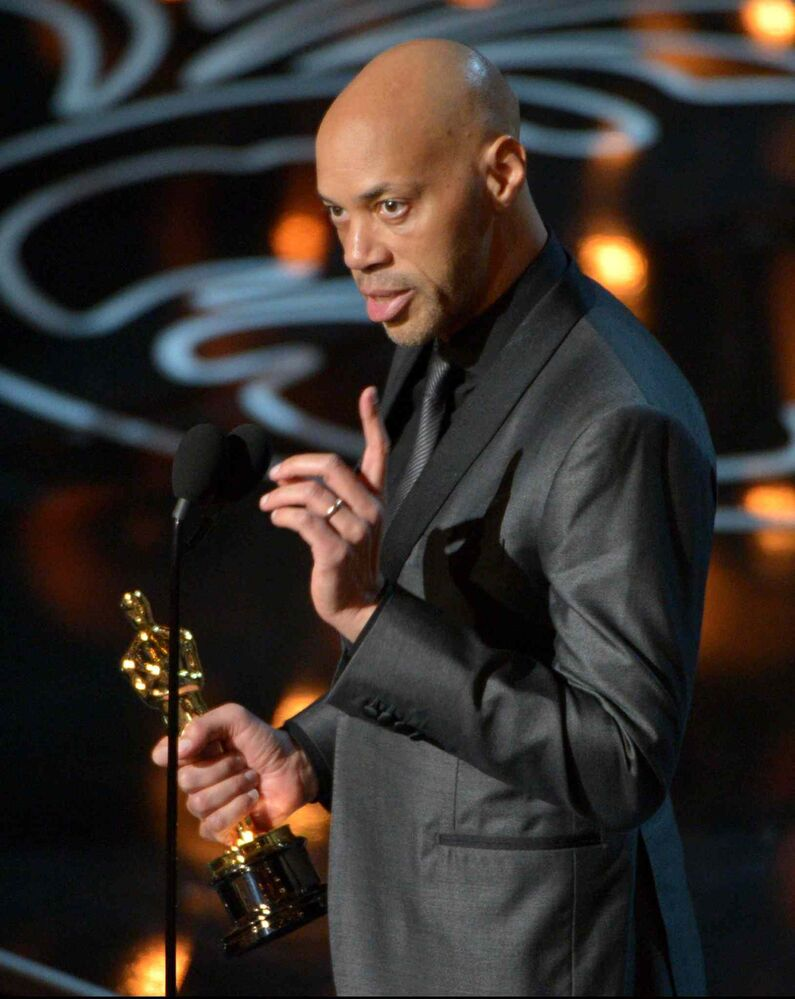John Ridley accepts the Academy Award for the best adapted screenplay of the year for 12 Years a Slave.   (John Shearer / The Associated Press)