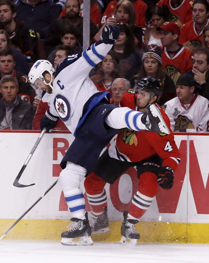 Winnipeg Jets left wing Andrew Ladd (16) and Chicago Blackhawks defenceman Niklas Hjalmarsson (4) collide along the boards. (Charles Rex Arbogast / The Associated Press )