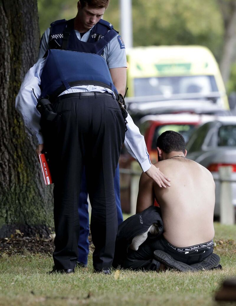 Police console a man outside a mosque in Christchurch, New Zealand following a deadly rampage that claimed the lives of at least 49 people. (Mark Baker / The Associated Press)