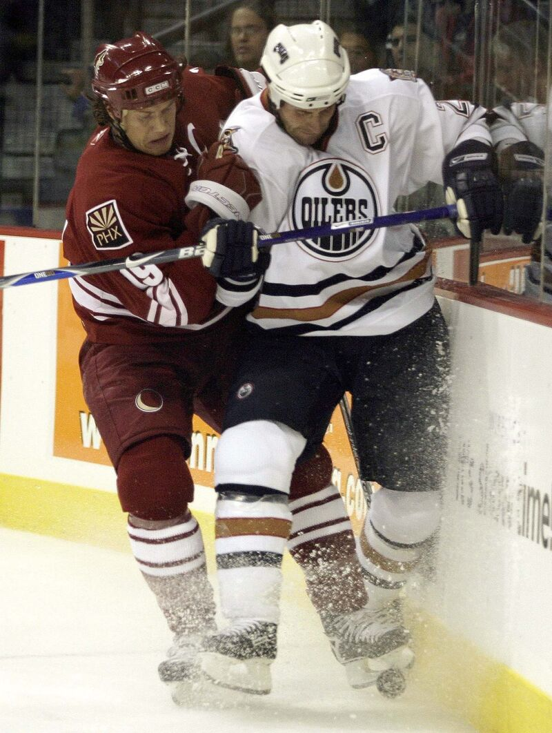 Edmonton Oilers Jason Smith (right) is checked by Doan.