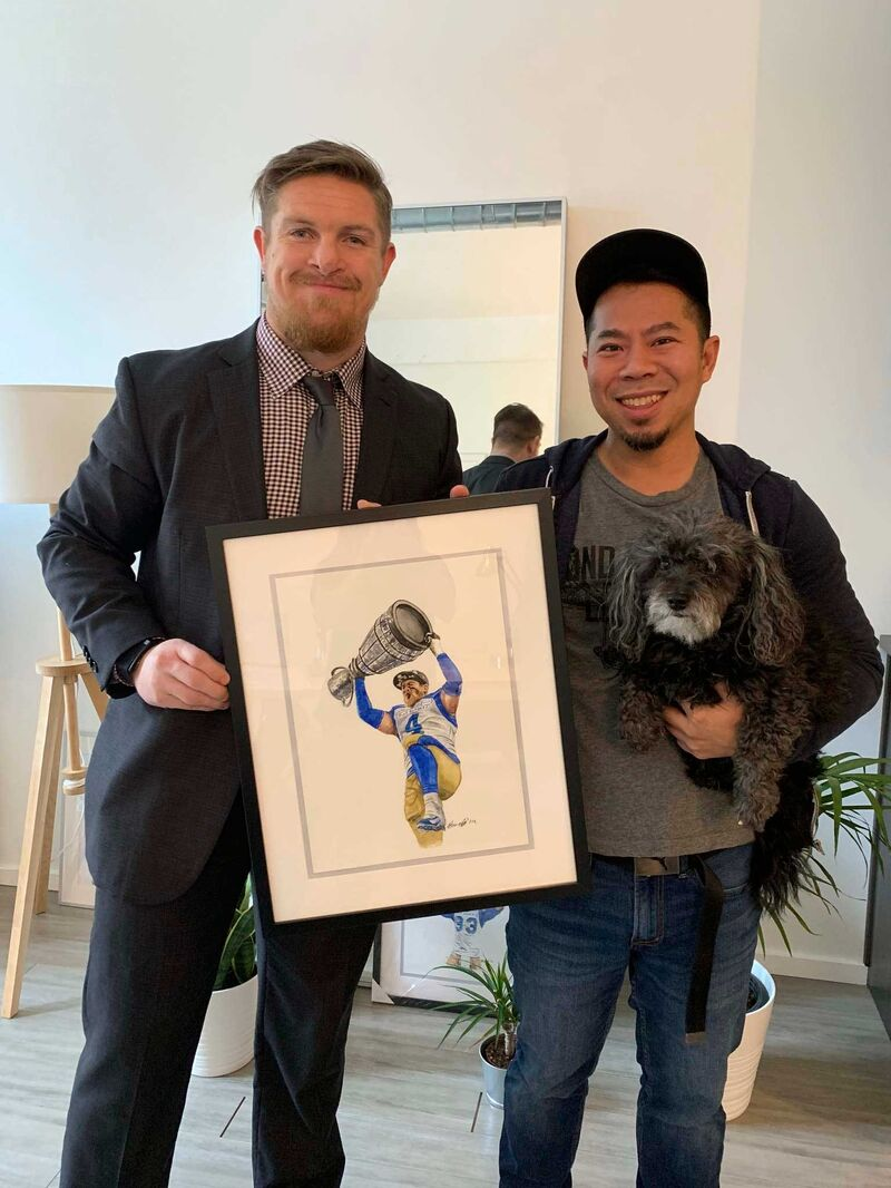 After seeing the portrait Nguyen painted of his Grey Cup win on Instagram, Blue Bombers linebacker Adam Bighill, left, stopped by to meet the artist.   (Supplied)