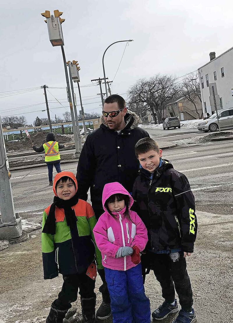 Parent Shane Connolly with his kids (from left) Colten, Xzandra, and Wyatt by Dufferin School Tuesday has to cross busy Isabel Street with them, even though there is a crossing guard on duty. Connolly said that flashing warning lights ahead of the pedestrian crosswalk might make it safer.