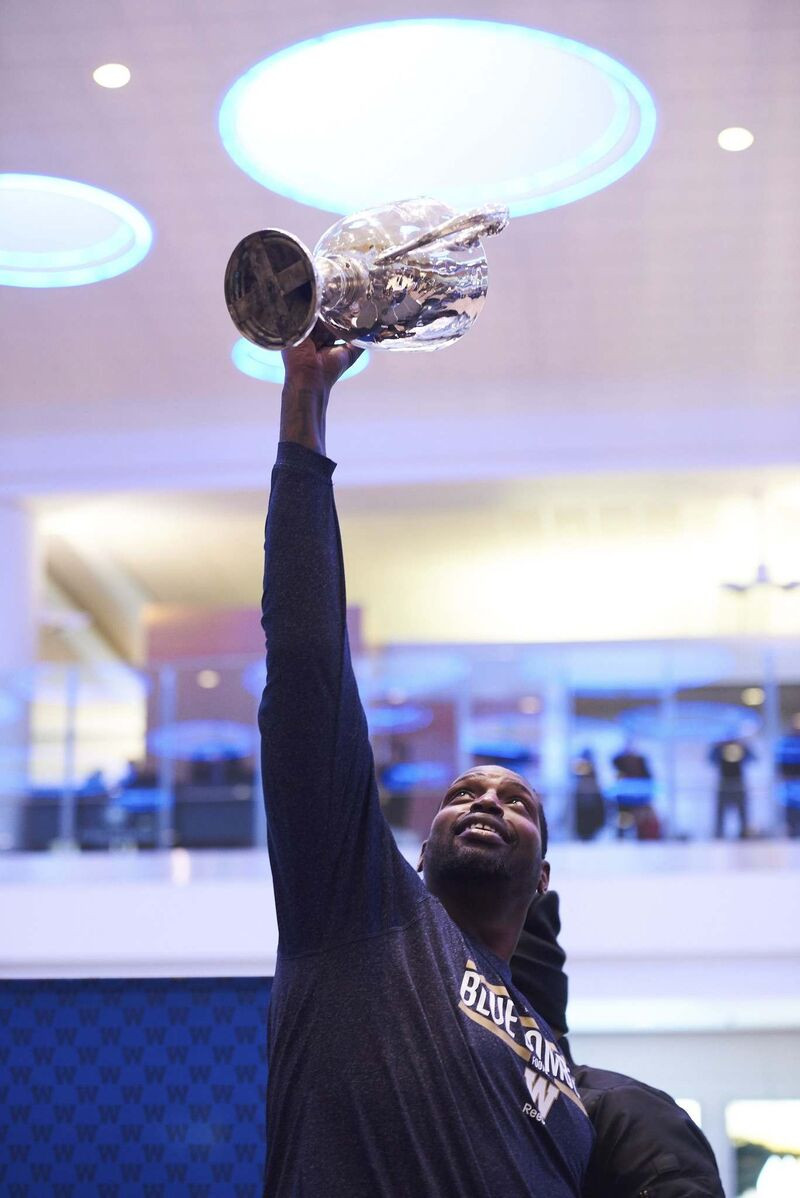 Hardrick hoists part of the Grey Cup trophy as the team arrives at the Winnipeg James Armstrong Richardson International Airport last year after winning the Grey Cup.