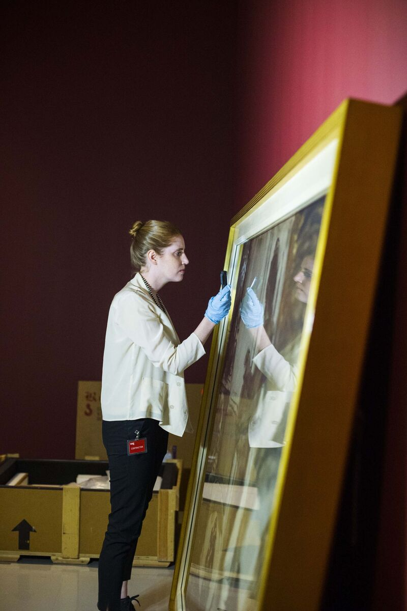 Conservator Erin Anderson inspects paintings as they are uncrated.