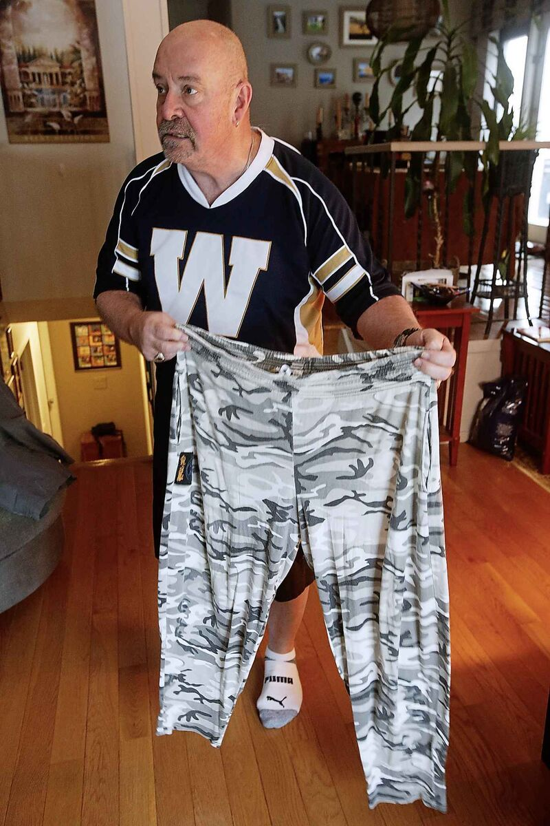 Much to the regret of his wife, Matthew shows off the parachute pants he will wear if the Blue Bombers win the Grey Cup on Sunday.  (John Woods / The Canadian Press)